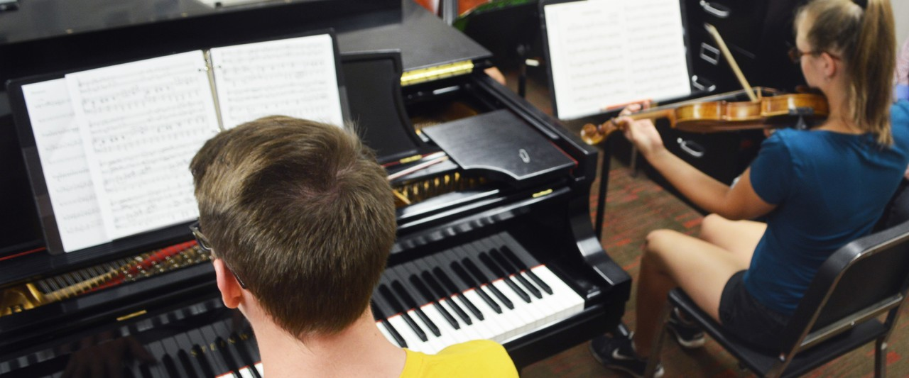 students playing in a work room on the piano, bassoon and violin