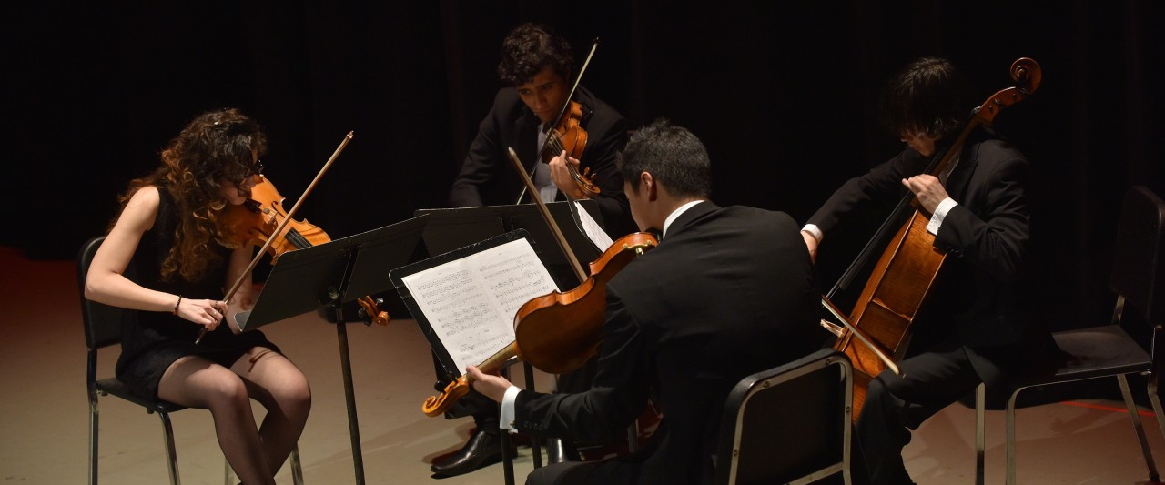 a female violinist with male violinist, violist, and cellist performing on Miller Auditorium's stage