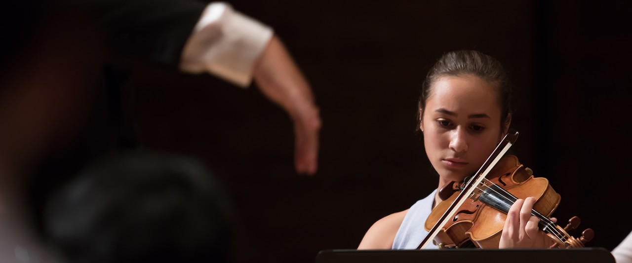 Picture of female violinist with conductors hand close to her face