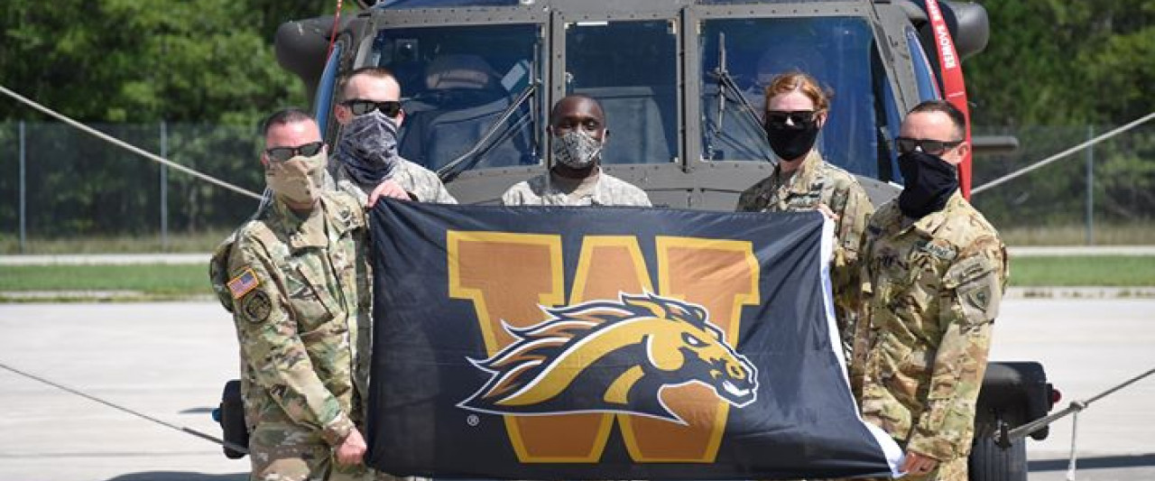 WMU military alumni holding a WMU flag in front of a helicopter