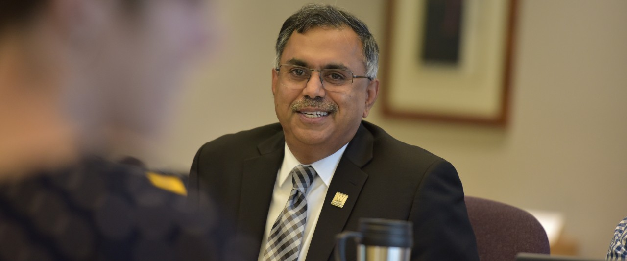 Photo of Satish Deshpande in a business suit, smiling and sitting in the conference room.