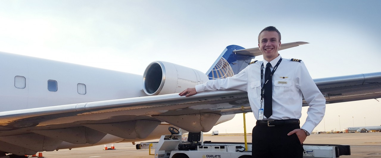 McCain standing in front of a SkyWest plane