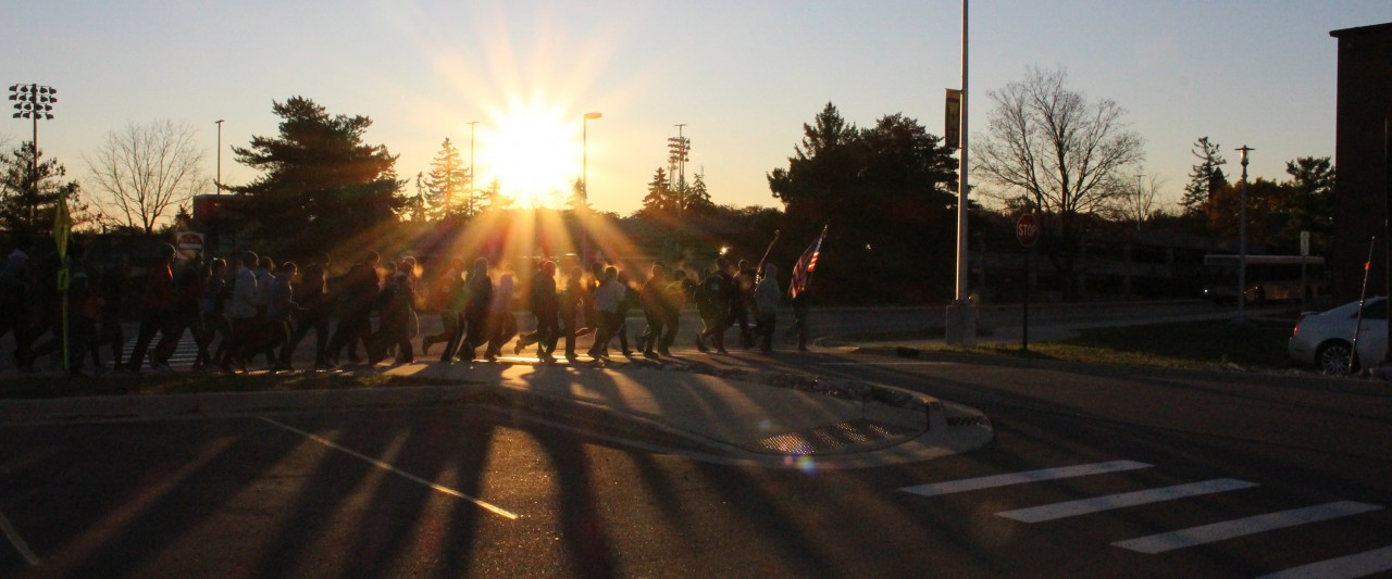 Students and staff participating in the Veterans Day Run. The sunrise causes the runners to appear as dark silhouettes, with only their breath being visible.
