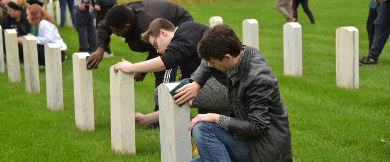 Students cleaning headstones
