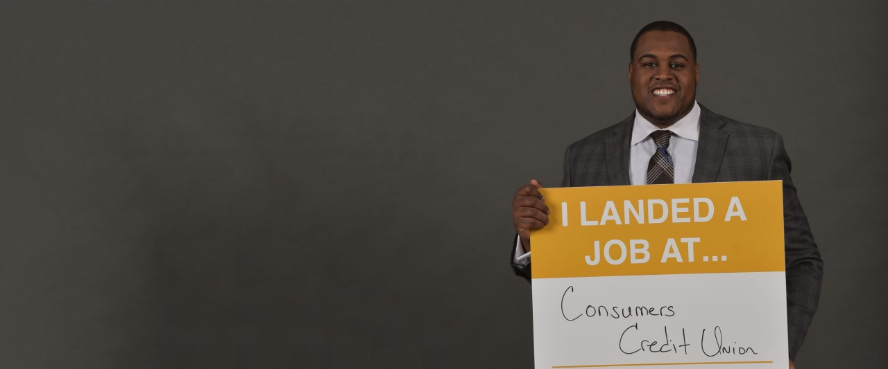 Student holding Consumers Credit Union sign