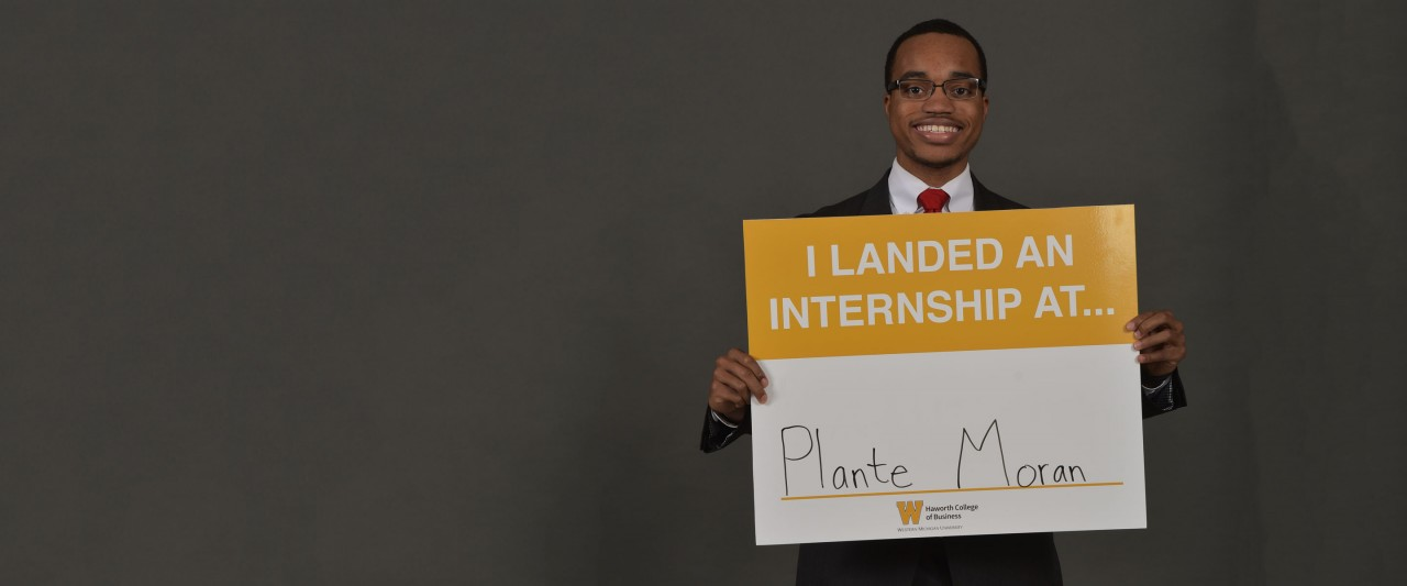 Student holding Plante Moran sign