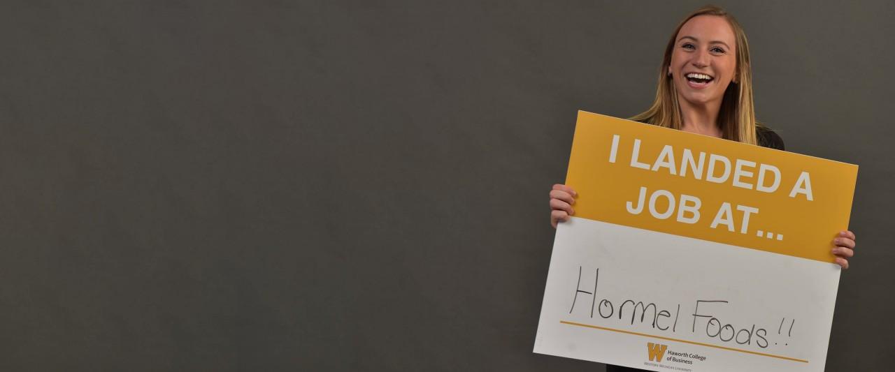 """Lauren Hillsburg holding a sign that reads """"I Landed a Job at Hormel Foods"""