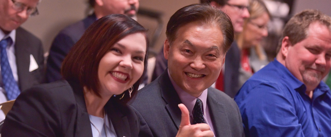 Rachel Larson and Mike Tarn, chair of BIS, giving the thumbs up. Both are smiling.