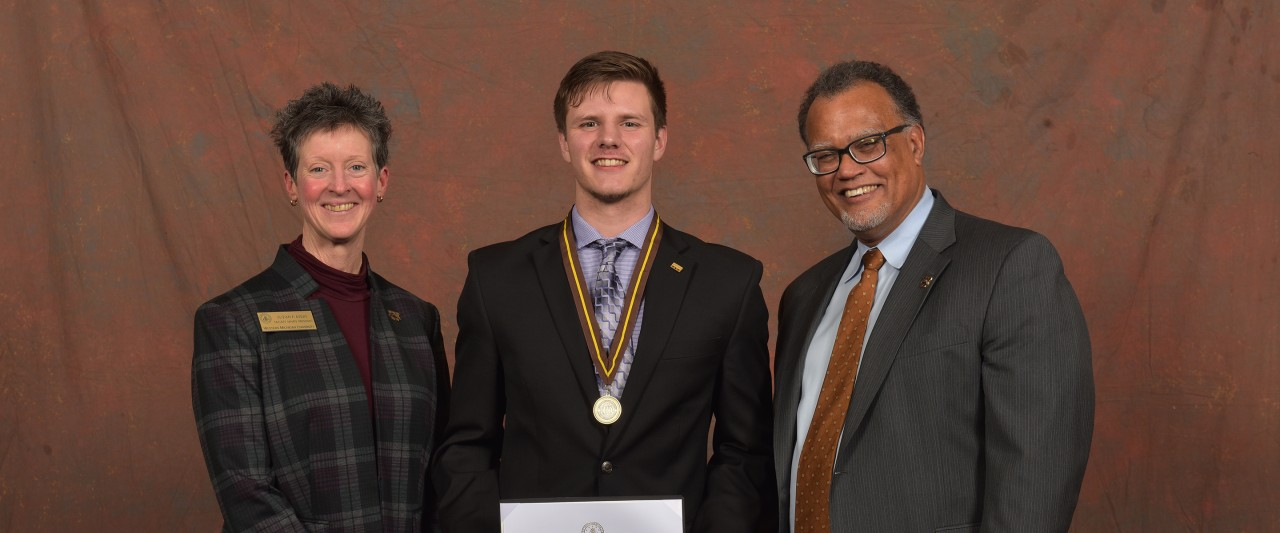 Mason Nelle with medal flagged by Faculty Senate President Suzan Ayers and WMU Presidental Edward Montgomery.