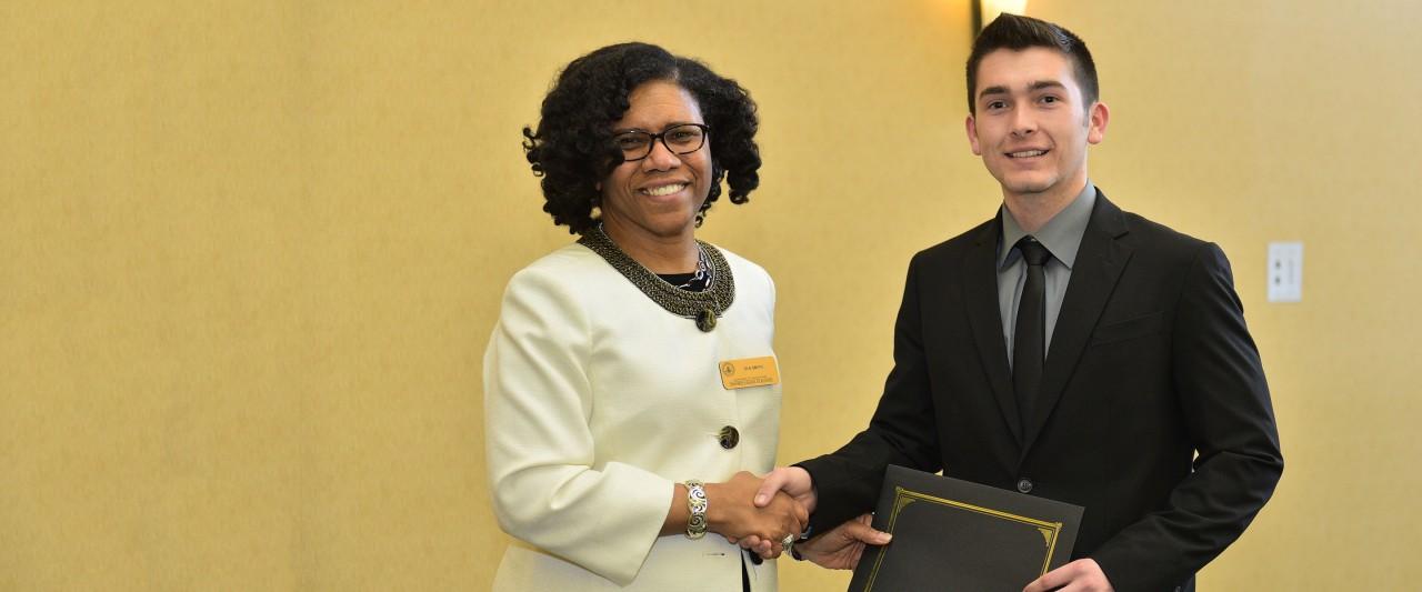 Dr. Ola Smith, chair, awarding scholarship to student