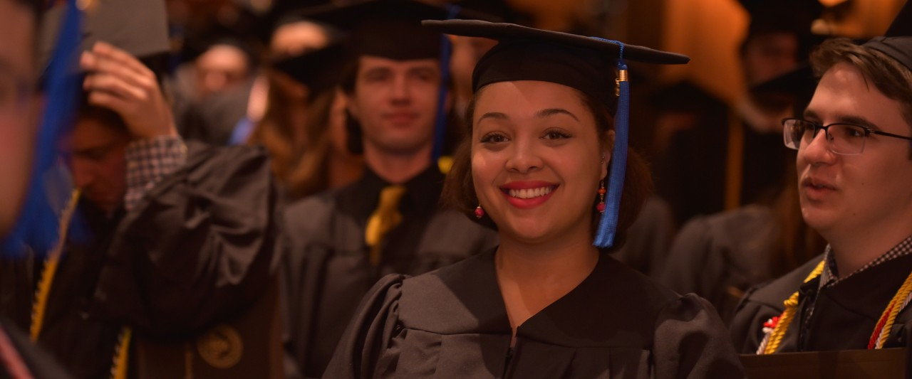 Focus on woman at commencement with large group of students in the crowd.