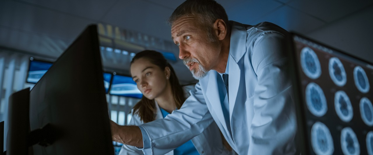 Man and woman looking at computer monitor in medical setting.