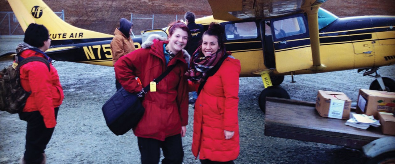 Accounting students in Alaska in front of airplane