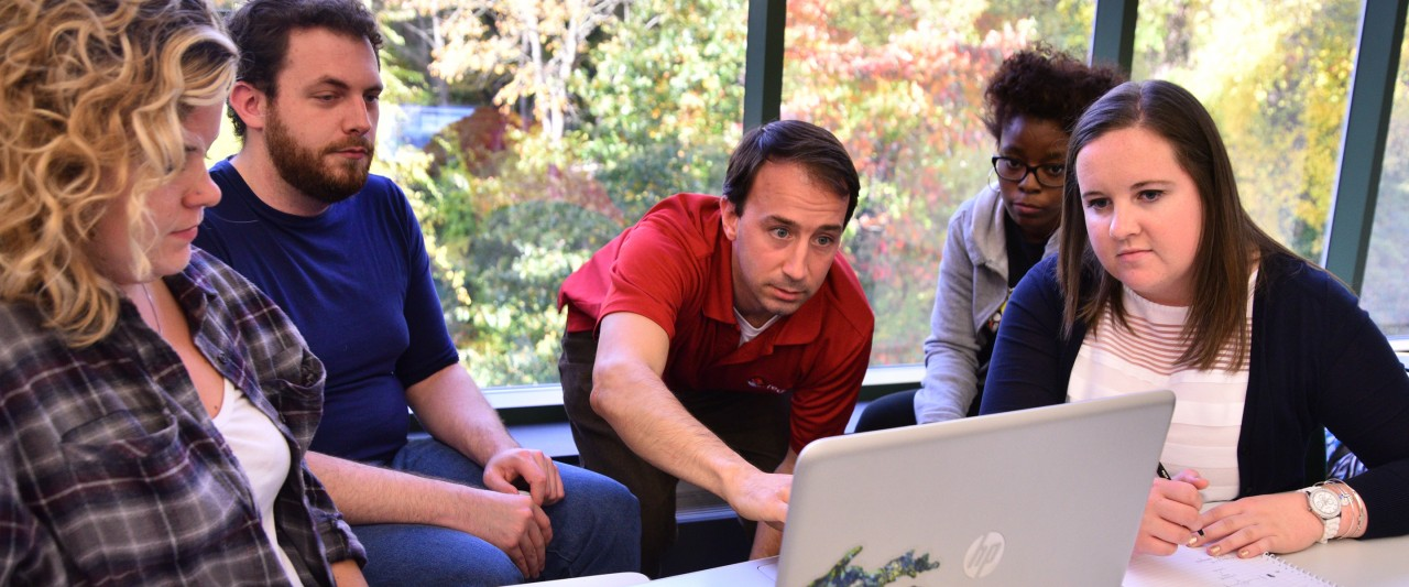 Faculty and students working at a laptop.