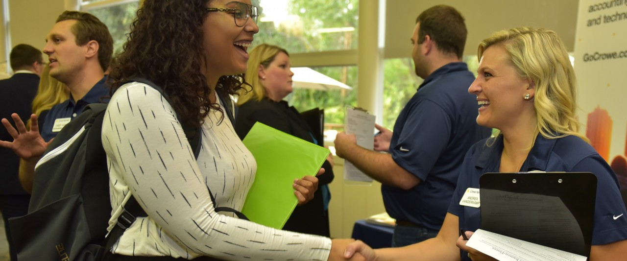 Student shaking hands with employer at career fair