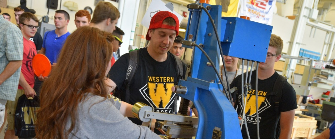 Students stamp WMU frisbees during CEAS fall welcome activities