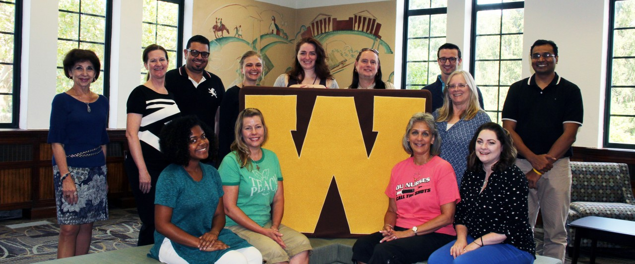 2017 Dissertation Cafe participants with Dr. Christine Byrd-Jacobs, Acting Dean of the Graduate College and Dr. Di Pierro, Program Manager for Graduate Research and Retention. A group of eleven diverse students surround a large gold W which pronounces the WMU brand. Walwood Hall, where the Graduate College is located, has been recently renovated with new carpet and furniture to host small and large groups. The original murals from 1939 can be seen behind the students