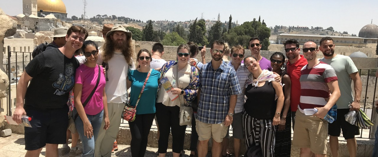 The nine W M U students visiting Jerusalem pose with four others in the city of Jerusalem.  The students and others all stand in a large semi circle and smile on a bright sunny day as the city stretches out behind them.  The view in the background is very different than what one might encounter here in Michigan.  A stone tower stands in the background in the left and next to it is the large golden Dome of the Rock, stone building tops fill the horizon.  There is little vegetation, the land is mainly arid dr