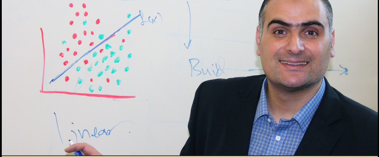 This photo shows Dr. Maabreth standing in front of a whiteboard in the front of a classroom.  He is smiling and holding a marker pointing out the word Linear.  On eat whiteboard is a coordinate graph plotting a large number of red and green dots that represent values for two different categories.  There is a blue line that runs at about a forty-five degree angle from the center bisecting the upper right quadrant and the red dots are mostly above the line whereas the green dots fall primarily below the line.