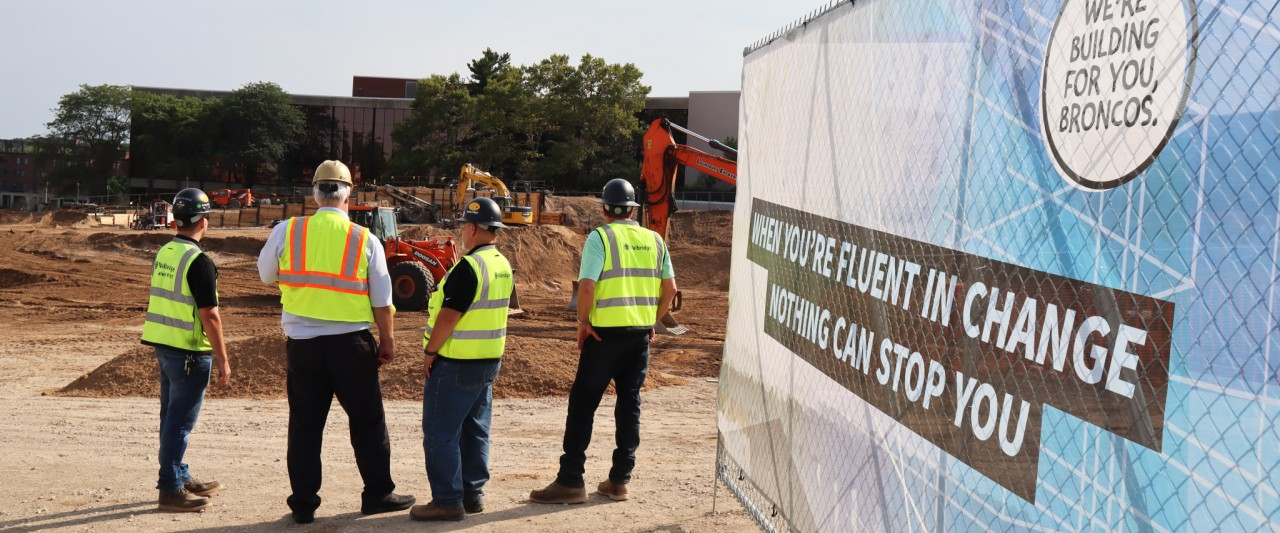 Four employees observing a construction site with a fence on the right.