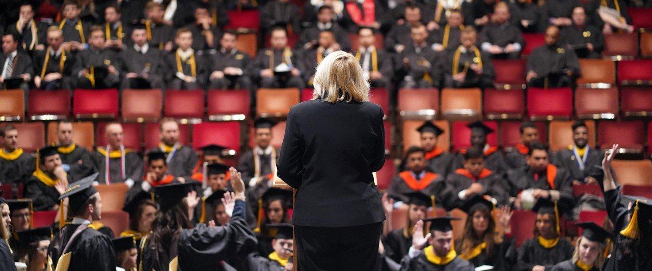 Many people in graduation regalia sitting in auditorium seats.
