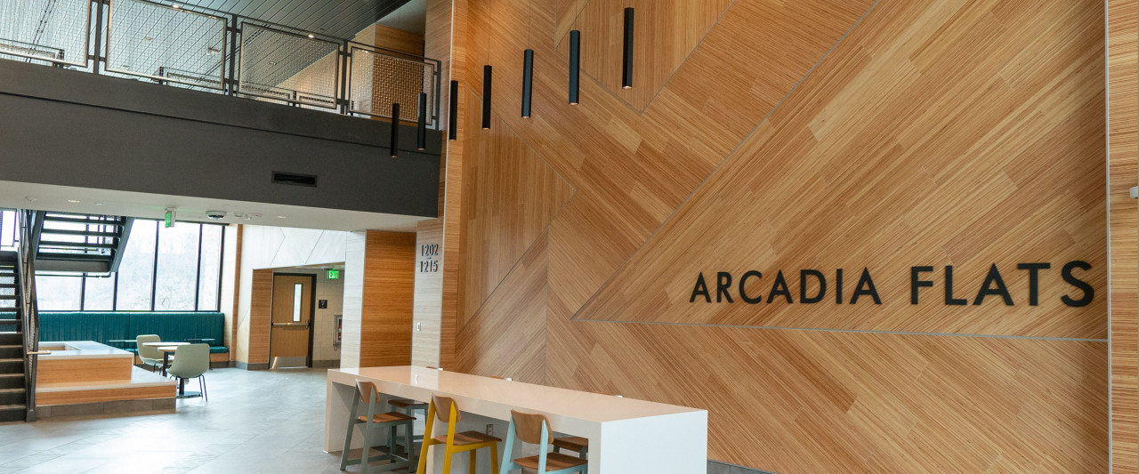 Lobby area with desk, chairs and staircase, with sign reading Arcadia Flats