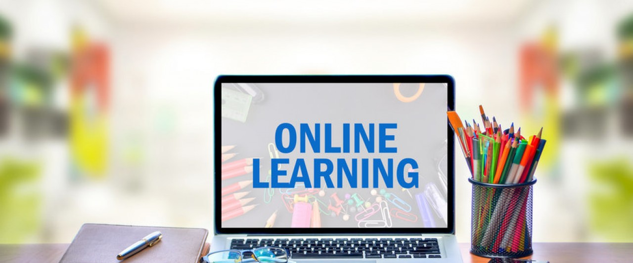 "Decorative: Laptop on desk, screen reads ""Online Learning"""