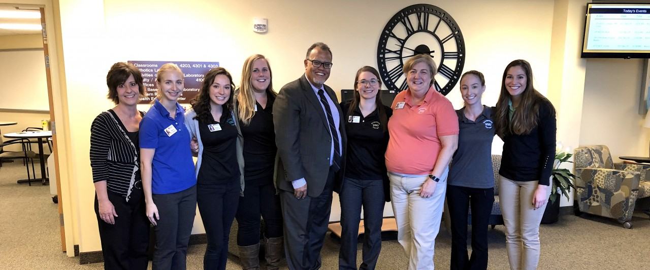 President Montgomery with eight women with the OT program in WMU-Grand Rapids.