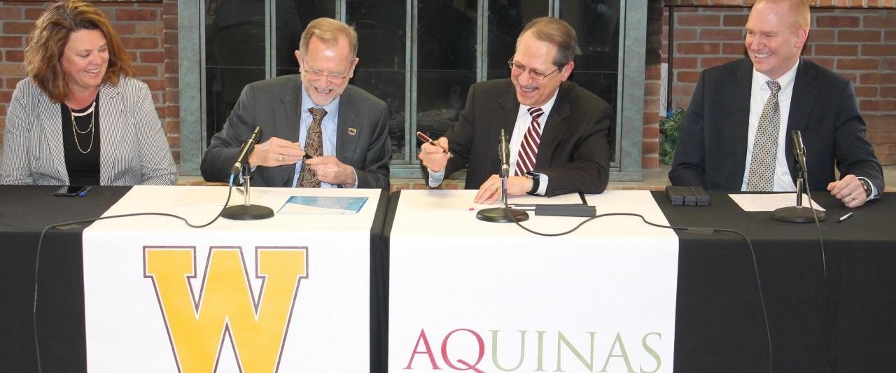 WMU and Aquinas College school officials signing partnership