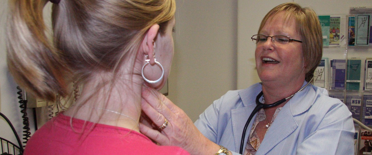 Photo of a clinician examining a patient.