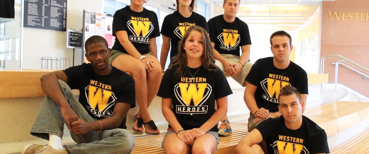 Group of students sitting on the steps inside Chemistry building. All are wearing Western heroes t-shirts