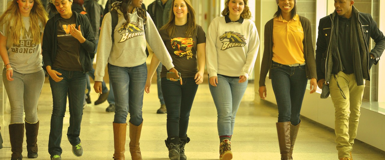 Students walking in Sangren Hall, chatting, smiling