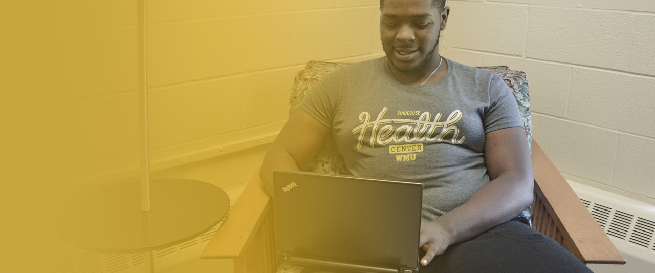 Student working on laptop, using telehealth services