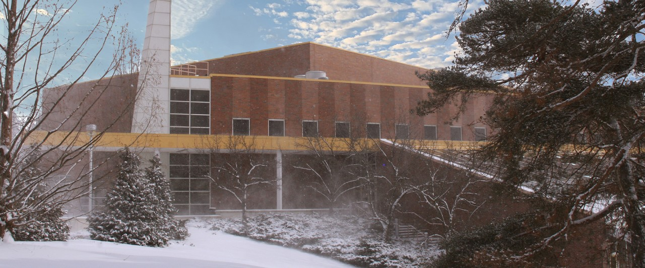 Front of Student Recreation building with snow, trees on the right side and a sunny sky with clouds