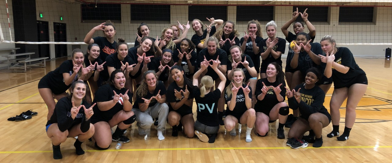 Mixed team photo of the Women's Volleyball club team, posing with their hands making the shape of a W