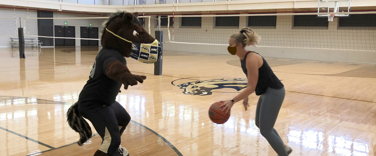 Buster playing basketball with Beth in masks in the SRC gym