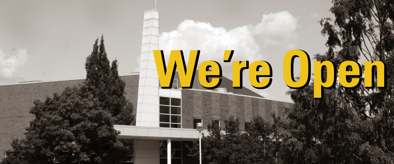SRC building in black and white with We're Open in big yellow letters