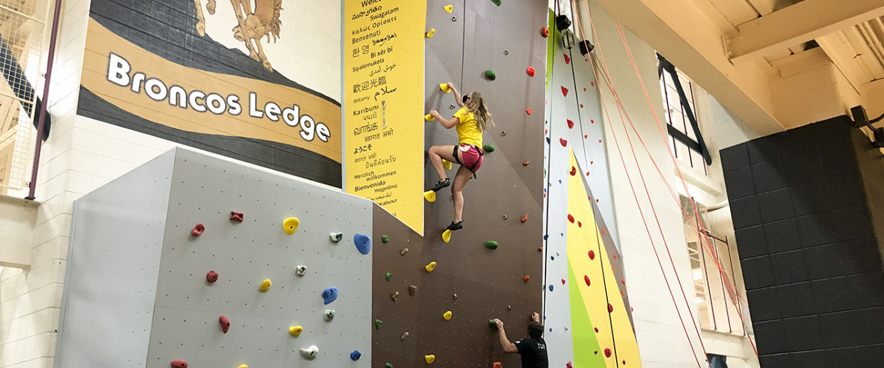 Student in shorts climbing the wall, near the Broncos Ledge and WMU welcomes you text along the side of the wall.