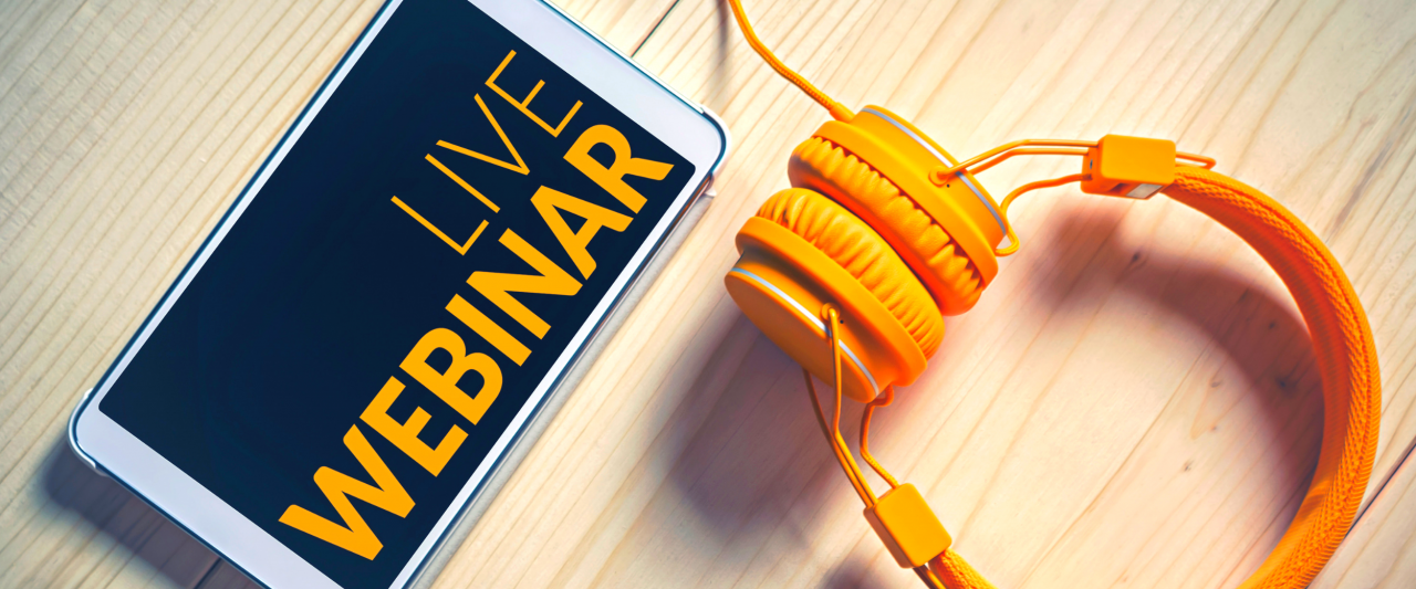 """Phone with """"live webinar"""" text and set of gold headphones"""