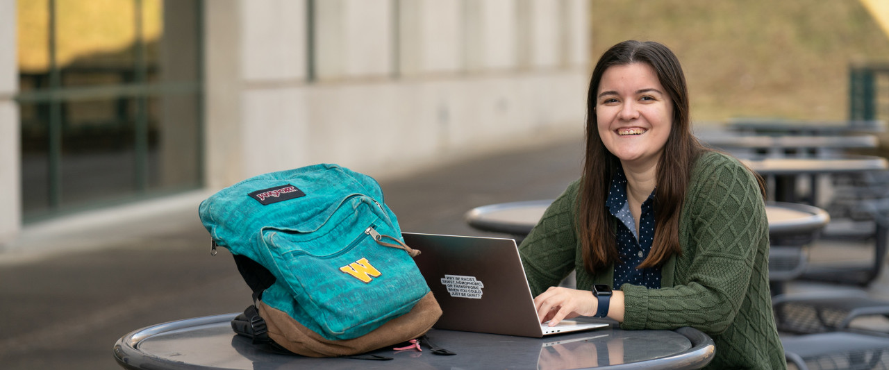 Student with laptop outside Schneider Hall