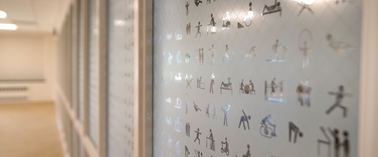 glass wall with etchings of different activities