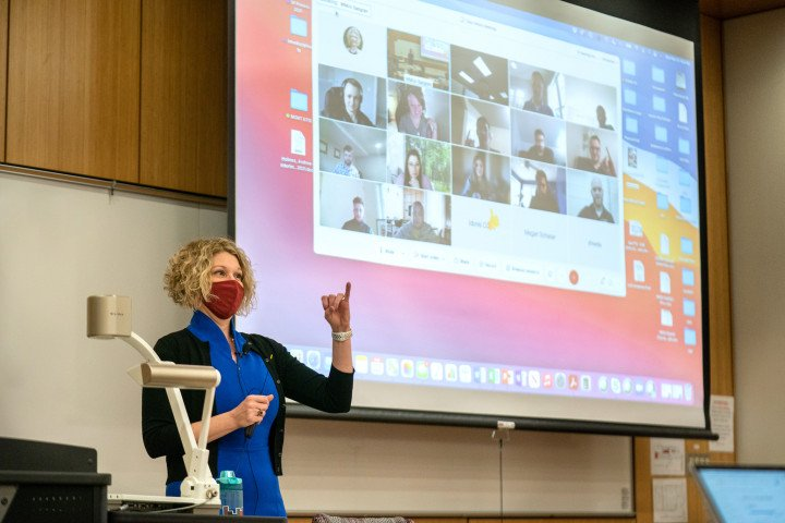 Dr. Jennifer Bott, masked, instructs virtual and in-person students in an MBA class, at the Haworth College of Business