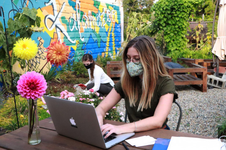 MBA students sits outside in flower garden with laptop