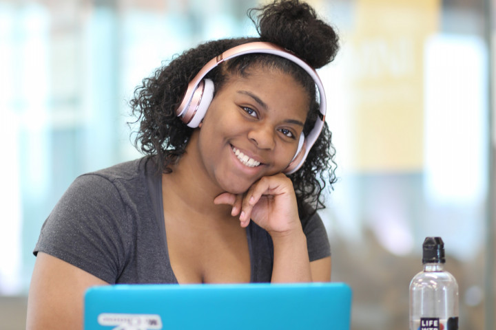 Student sitting at laptop with headphones