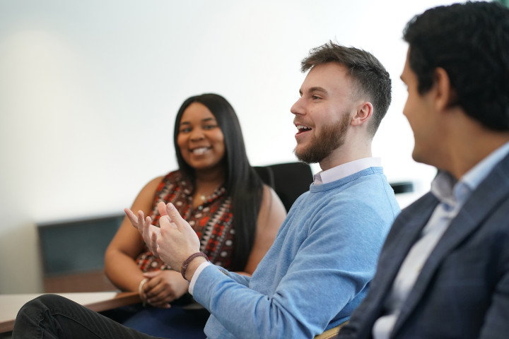 Three students dressed in business attire sitting in conference room smiling