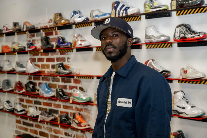 Pictured is Frederick Paul standing in front of wall of shoes