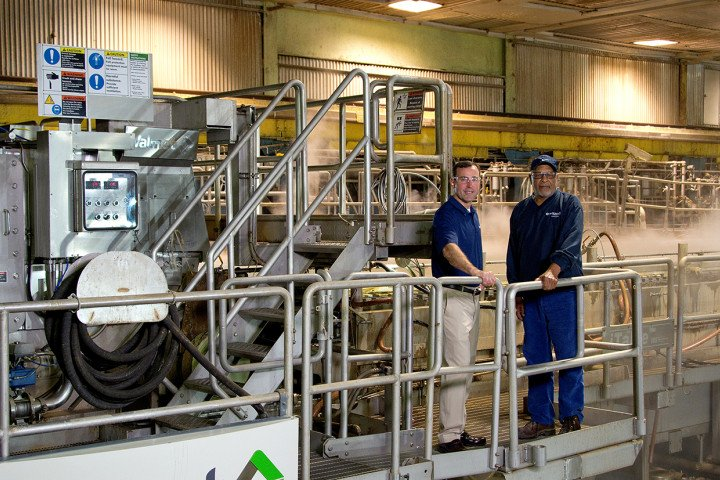 Pictured is Mike Doss and employee standing in front of large paper mill machine