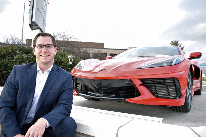 Pictured is Steven Ross sitting in front of a red car