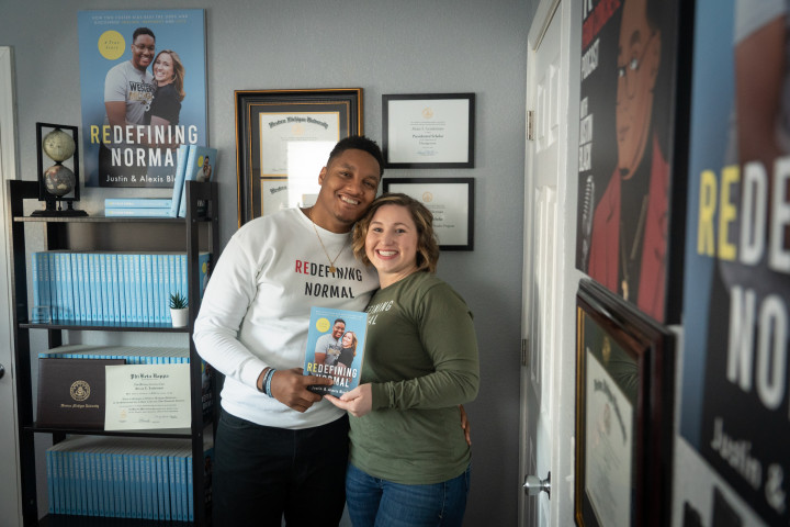 Justin and Alexis Black hold a copy of their book while standing next to a book shelf.