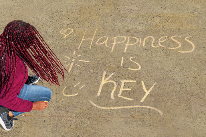 """A student writes """"happiness is key"""" in chalk on a sidewalk."""